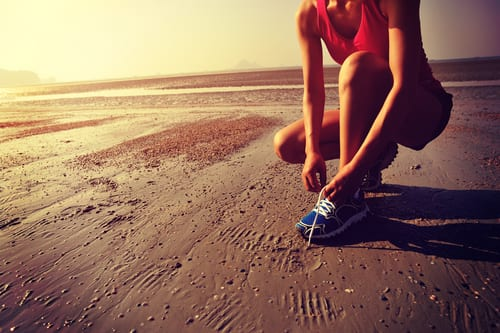 woman runner tying shoelace before running on beach-img-blog