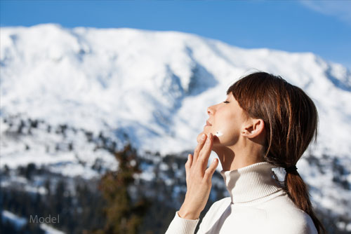 A woman applies lotion to her skin amid a winter background. Winter temperatures can strip skin of hydration, causing skin to look lifeless and dull.