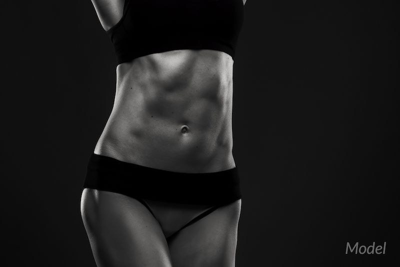 fitness woman with abdomen close-up, black and white photography.