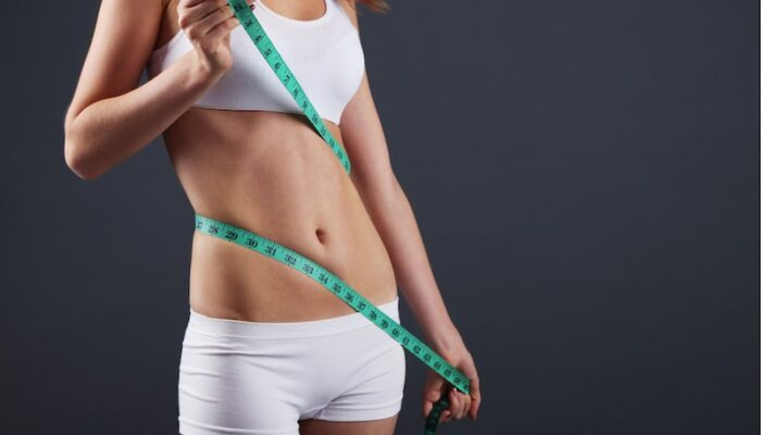 woman measuring her stomach with tape