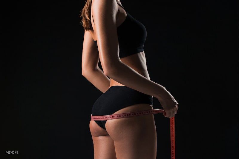 Woman against a black background wrapping a tape measure around her buttocks.